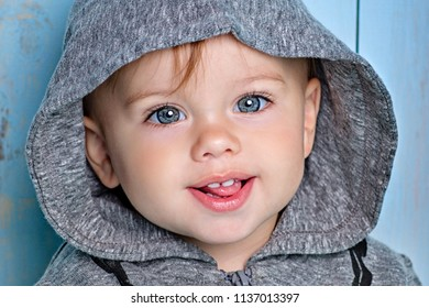 Sweet baby boy, closeup portrait of child isolated on wood background, cute toddler with blue eyes