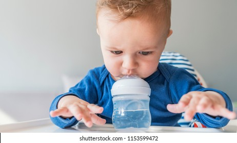 Sweet baby boy holding bottle and drinking water. Baby drinking water from bottle sitting in the highchair. Baby holding bottle