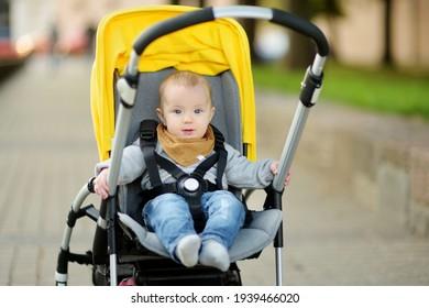 Süße Baby-Junge sitzt in einem Roller im Freien. Kleines Kind im Kinderwagen. Kleinkind im Kinderwagen. Der Sommer geht mit Kindern. Familienurlaub mit kleinen Kindern.