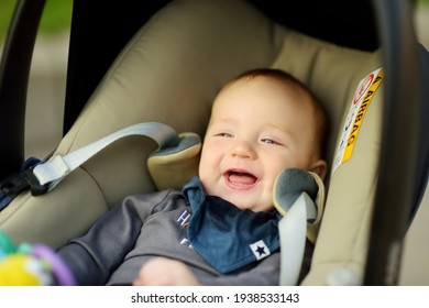 Sweet baby boy smiling happily in a car seat. Infant being carried in a car seat. Family leisure with little child.