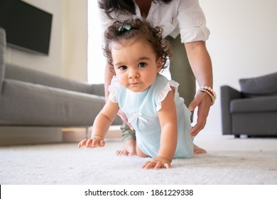 Sweet baby crawling on floor at home, hands of mom going to take child in arms. Parenthood and childhood concept