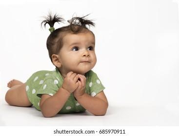 Sweet, baby girl lying on stomach in green, polka dot onesie on white background