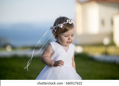 Sweet baby girl playing outdoors. Baptism, Wedding & Fashion