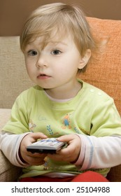 sweet baby girl with remote control on sofa