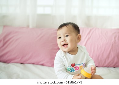 Sweet baby girl sitting on bed at home.