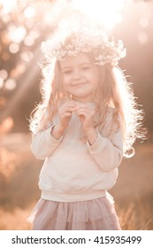 Sweet baby girl standing in sun light outdoors.