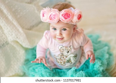 Sweet baby girl in a wreath of pink roses, closeup portrait of cute 8 month-old smiling girl,  toddler