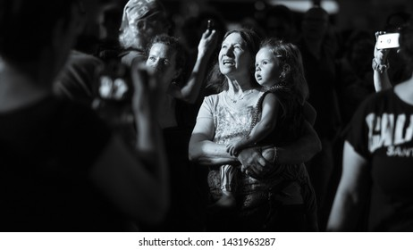 A sweet baby sits comfortably on her grandmom's hands looking towards the light during a street dance party, June 21st, 2019, Tel Aviv, Israel.