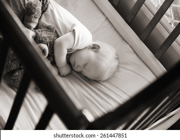 sweet baby sleeping in his crib with his teddy bear in black and white