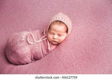 sweet baby sleeping on a pink blanket
