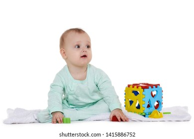 c0d541e2 Sweet baby wearing green romper suit plays with children toy on a white  background. Early