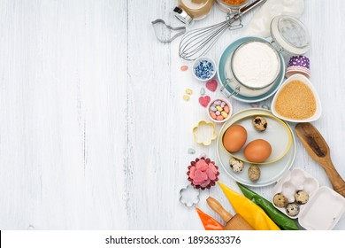 Sweet baking concept for Easter. Cooking background with rolling pin, eggs, whisk for whipping, cookie cutters, sugar sprinkling, flour. Rustic white wooden background, top view copy space.
