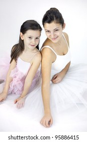 Sweet ballerina girl in a white background in a studio