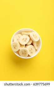 Sweet bananas in bowl on yellow background