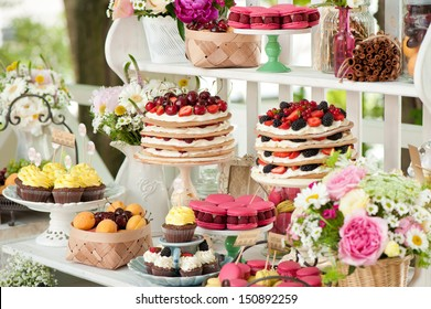 Sweet bar on summer wedding. Layer cakes with protein cream and fresh cherry and berries on a cake stand outdoors