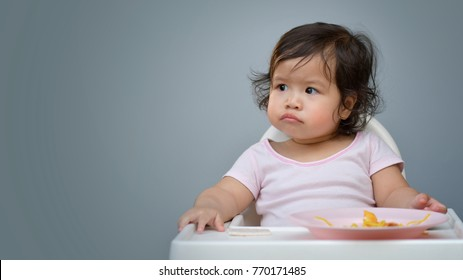 Sweet beautiful baby girl bored with food.bored kids. Baby girl  looks with disgust for food. Girl bored eating.