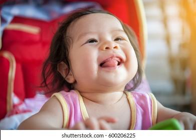 Sweet Beautiful baby girl in red baby cart, Joyful, Happy, Excited.