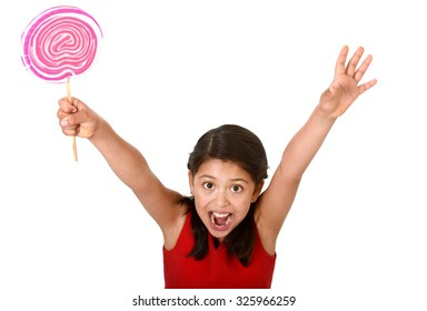 sweet beautiful latin female child holding big pink spiral lollipop happy and excited isolated on white background in funny crazy face expression and sugar addiction concept