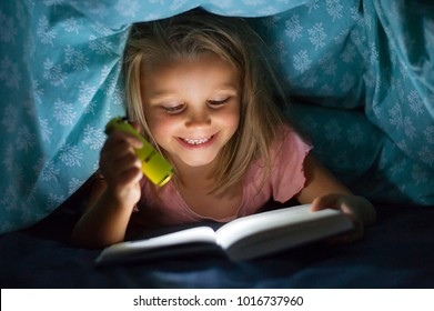 sweet beautiful and pretty little blond girl 6 to 8 years old under bed covers reading book in the dark at night with torch light smiling happy hidden covered by sheets excited and cheerful