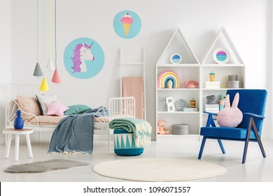 Sweet bedroom interior for a kid with a blue armchair, rabbit pillow, bed, unicorn, ice-cream posters and shelves