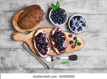 Sweet berry crostini sandwiches with blackberry jam and berries blueberries, whole grain bread for sandwiches, sandwiches board, spoon, mint leaves on a bright white background wooden, top view