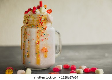 Sweet berry milkshake with whipped cream, dripping sauce and candy