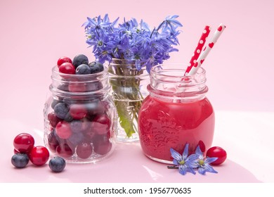 Sweet berry and smoothie on pink background