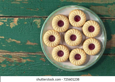 Sweet biscuits with raspberry jam and vanilla flavor in plate on old green wooden background, top view. Space for text