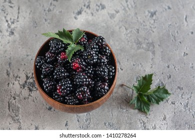 Sweet blackberry and leaves in wooden bowl on grey stone background. Top view.