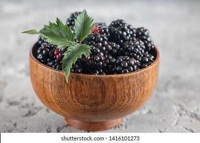 Sweet blackberry and leaves in wooden bowl on grey stone background.