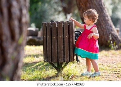 Sweet blond little baby girl throwing garbage into recycle bin, Ecology pollution people concept