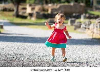 Sweet blond little baby girl in beautiful dress plays walks outdoors. Famous Archaeological Site of Olympia. Peloponnese, Greece. Travel concept