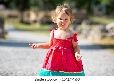 Sweet blond little baby girl in beautiful dress plays walks outdoors on warm sunny summer day