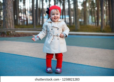 Sweet blond little toddler girl in beautiful beige trench coat and red cap plays outdoors at playground on warm sunny spring day