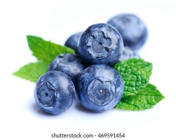 Sweet blueberries with mint leaves close up .