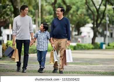 Sweet boy in casual outfit walking along street path with smiling father and grandfather after shopping on sunny day