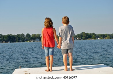 a sweet boy and girl hold hands while gazing out on the water