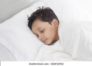sweet  boy sleeping in bed, happy bedtime in white bedroom.  Sleeping child