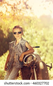 sweet boy with sunglasses standing leaning on an old motorcycle, the day is colored red warm yellow colors