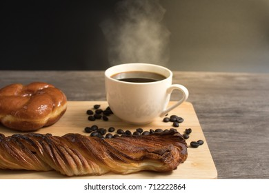 Sweet bread and honey danish and a cup of coffee and coffee seed on rustic wooden table with sun flare