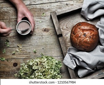 Sweet bread, typical Slovak cake. Woman's hand stiriing cocoa milk and dry hyndrangea flower on vintage wooden background. Overhead shot.