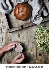 Sweet bread, typical Slovak cake. Woman's hand stirring cocoa milk and dry hyndrangea flower on vintage wooden background. Overhead shot.