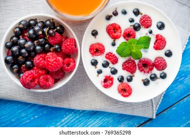 sweet breakfast with healthy food with fruit and yoghurt on blue wood table
