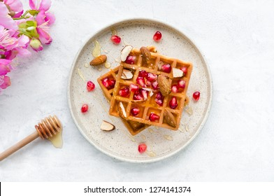 Sweet breakfast with homemade waffles, honey and fresh pomegranate on concrete table. Top view.