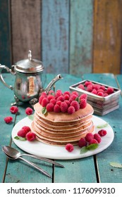 Sweet breakfast. Pancakes with raspberry jam and fresh berries on wooden table. Closeup food photo.