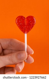 Sweet bright red lollipops in woman's hand on bright orange background. Copy space.