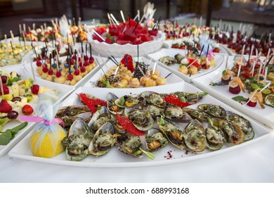 sweet buffet table. Beautifully decorated catering banquet table with burgers, profiteroles, salads and cold snacks. Variety of tasty delicious snacks on the table
