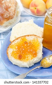 Sweet bun with apricot jam and fresh apricots for breakfast vertical