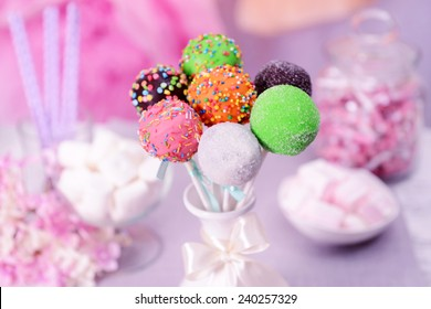 Sweet cake pops in vase on table on bright background