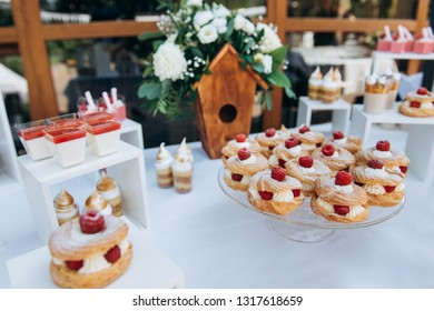 Sweet cake with raspberries and cream on beautiful wedding candybar background